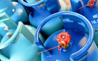 Group of blue propane tanks with red knobs